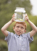 Young boy looking at frog in glass jar outdoors — Stock Photo