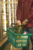 African American man holding shopping basket at grocery store — Stock Photo