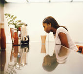 Woman drinking milkshake at diner counter — Stok fotoğraf