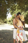 Couple kissing in a grove of trees — Stock Photo