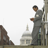 Businessman using cell phone in urban area — Stock Photo