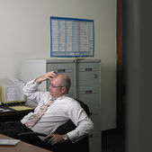 Middle-aged businessman thinking at his desk — Stock Photo