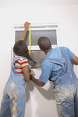 Rear view of couple measuring window — Stock Photo