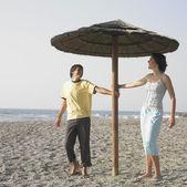 Młoda para śmiejąc się pod parasolem na plaży — Zdjęcie stockowe