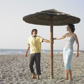 Young couple laughing underneath umbrella on beach — Stok fotoğraf