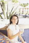 Hispanic woman with drink at hotel bar — Stockfoto