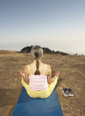 Senior woman meditating on a yoga mat outdoors — Stock Photo