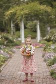 Dziewczynka gospodarstwa kwiaty w ogrodzie — Zdjęcie stockowe