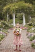 Girl holding flowers in garden — ストック写真