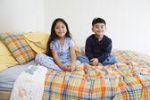 Hermano y hermana sentada en la cama juntos — Foto de Stock