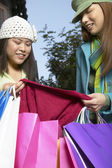 Woman showing female friend her new clothes — Stock Photo