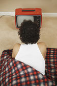 Young man in a sleeping bag watching TV — Stock Photo