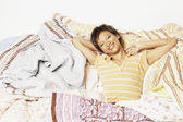 Young woman relaxing among blankets — Stock Photo