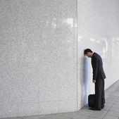 Businessman leaning head on wall — Stock Photo