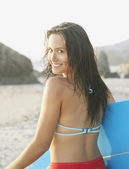 Rear view portrait of woman at beach carrying surf board — Stock Photo