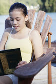 Teenage girl sitting on deck by lake reading — Stock Photo