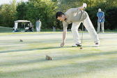 Picking up ball on putting green — Stock Photo