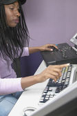 African American woman using computer and recording equipment — Stock Photo