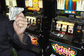 Young man holding his winnings at the casino — Stock Photo