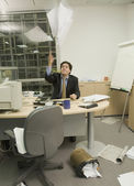 Hispanic businessman throwing paperwork in messy office — Stock Photo
