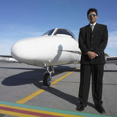 Businessman standing next to nose of airplane — Stock Photo