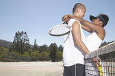 Couple hugging on tennis court — Stock Photo