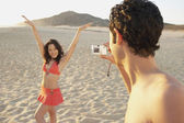 Man taking photograph of woman on the beach — Stock Photo