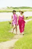 Two women walking on beach — Stock Photo