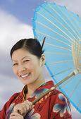 Middle-aged Asian woman in traditional dress with parasol — Stock Photo