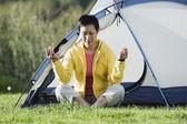 Woman sitting outside tent meditating — Stock Photo