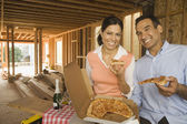 Hispanic couple having pizza and champagne at construction site — Stock Photo
