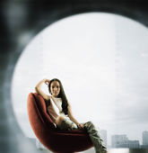 Portrait of a young woman sitting on couch with her hand on her head — Stock Photo