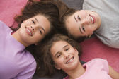 High angle view of Hispanic sisters laying on floor — Stock Photo