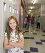 Young girl smiling in school hallway — Stock Photo