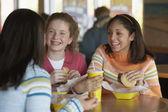 Teenage girls eating at restaurant — Stock Photo