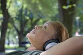 African woman wearing headphones in park — Stock Photo