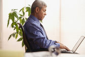 Mature businessman using a laptop — Stock Photo