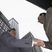 Low angle view of businessmen shaking hands — Stock Photo