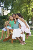 African mother and young daughters hugging outdoors — Stock Photo