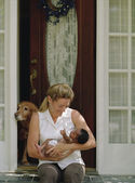 Woman holding a newborn baby on her doorstep — Stockfoto