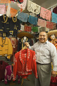 Senior Hispanic man holding a matador outfit — Photo