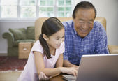 Asian grandfather and granddaughter looking at laptop — 图库照片