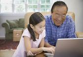 Asiatiska farfar och barnbarn tittar på laptop — Stockfoto