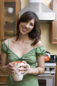 Portrait of woman standing in kitchen holding mug — Stock Photo