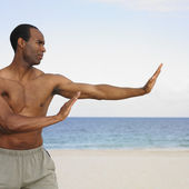 African man stretching on beach — Stock Photo