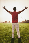 Male athlete holding his arms out on football field — Stock Photo