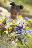 Young African American girl holding bouquet of flowers outdoors — Stock Photo