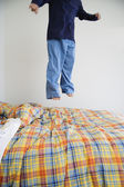 Boy jumping on bed — Stock Photo