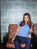 Portrait of a young woman sitting on a couch — Stock Photo