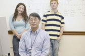 Male teacher with two students — Stock Photo